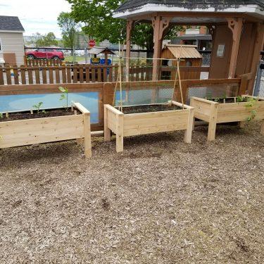 Trois bacs en bois remplis de terre sont disposés dans une cour de garderie.