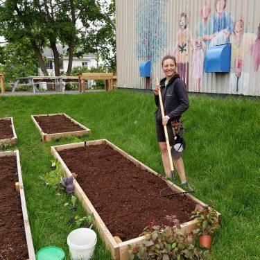 Une horticultrice sourit en passant le râteau dans un jardinet.