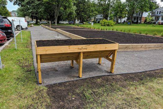 Un bac de culture surélevé est posé devant des parcelles de jardin communautaire.