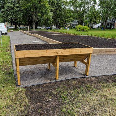 Un grand bac de culture surélevé, en bois, est rempli de terreau. À l'arrière, deux grandes parcelles de terre ont été préparées pour un jardin communautaire.