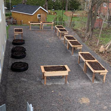 Une dizaine de bacs de culture surélevés et quelques pots de géotextile sont disposés sur une cour de gravier, à l'arrière d'un bâtiment.