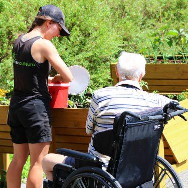 Une horticultrice, debout, et un homme âgé, assis dans une chaise roulante, sont vus de dos alors qu'ils entretiennent des plantes dans un bac de culture surélevé.