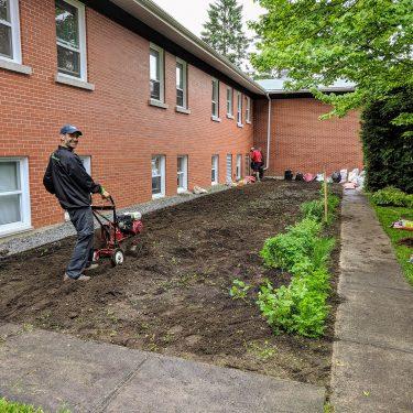 Un horticulteur passe le rotoculteur sur une parcelle de terrain, derrière un bâtiment de brique rouge.