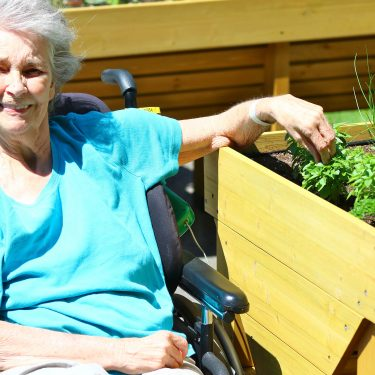 Une femme âgée, en chaise roulante, sourit à la caméra tout en touchant une petite plante dans le bac de culture à son côté.