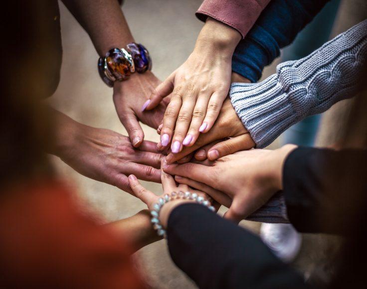 Sept mains de différentes personnes sont empilées les unes sur les autres dans un geste de support collectif.