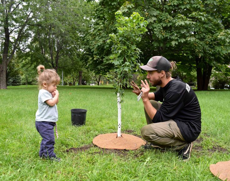 Un animateur accroupi près d'un jeune arbre interagit avec une fillette.