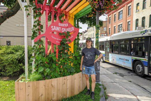 """Une jeune femme se tient à côté d'un bac où poussent des plantes grimpantes, sur des tuteurs de bois colorés formant une insigne à l'entrée de la rue St-Vallier Ouest. Une affiche en forme de feuille indique """"Quartier Saint-Sauveur""""."""