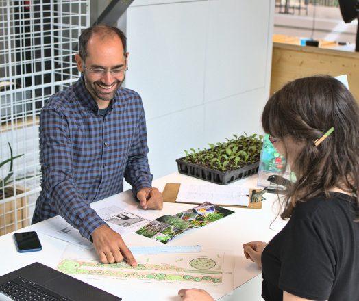 Un conseiller souriant montre un plan de jardin à une cliente.